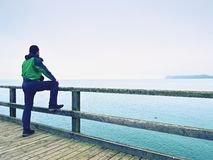 Man thinking. Tourist in green on sea mole at handrail. Autumn mist. Man thinking. Tourist in green on sea mole at wooden handrail. Autumn misty day. Touristic royalty free stock photography