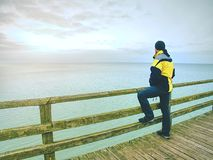 Man thinking. Tourist in warm clothes on sea mole at handrail. Tourist on pier in harbor. Man thinking. Tourist in warm clothes on sea mole at wooden handrail stock images
