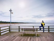Man thinking. Tourist in warm clothes on sea mole at handrail. Tourist on pier in harbor. Man thinking. Tourist in warm clothes on sea mole at wooden handrail royalty free stock photos