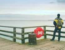 Man thinking. Tourist in warm clothes on sea mole at handrail. Tourist on pier in harbor. Man thinking. Tourist in warm clothes on sea mole at wooden handrail royalty free stock image