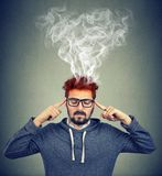 Man thinking very intensely having headache with steaming coming out. On gray wall background Royalty Free Stock Photos