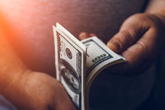 Man thinks cash dollar bills, sunlight effect, toned. Making cash money success concept Stock Photos