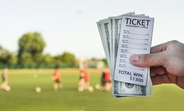 A man thinks the money he won against the backdrop of the stadium where he plays football, sports betting, close-ups. Bookmaker`s ticket royalty free stock images