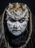 Man with thorns or warts, face covered with glitters. Demon with golden hood on black background. Senior man with white stock image
