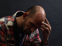 Man in Thought. A man in deep thought holds his head in his hand. Over black Stock Photography