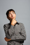 Man in thoughtful pose on grey background Royalty Free Stock Images