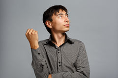 Man in thoughtful pose on grey background Royalty Free Stock Photos