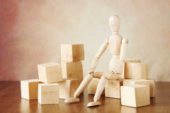 Man thoughtfully sits among big blocks. Conceptual image with wooden puppet Stock Images