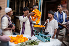 Man threading colourful flower garlands in Delhi Royalty Free Stock Photo