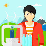 Man with three D printer. An asian man standing near 3D printer making a smartphone using recycled plastic on the background of solar panels and wind turbines Royalty Free Stock Photos