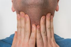 Man with throat sore is holding his aching throat. Body pain concept Stock Image