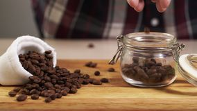 Man throw roasted coffee bean from hand into jar closeup with white bag near 4K. Man throw roasted coffee bean from his hand into jar closeup with white bag near stock video