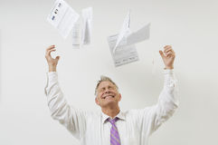 Man Throwing Bills In The Air. Senior businessman throwing bills isolated over white background Stock Image