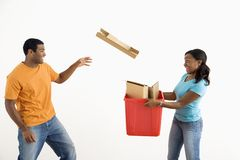 Man throwing cardboard into bin. stock images
