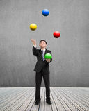 Man throwing and catching colorful balls. On wooden floor with concrete wall Stock Photo