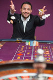 Man throwing chips onto roulette table Stock Image