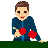 Man Throwing Dice. Handsome young man throwing dice gambling playing craps on green table Royalty Free Stock Photo