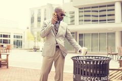 Man throwing empty paper coffee cup in recycling bin Stock Image