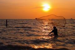 Man throwing the fishing net. During sunset Stock Images