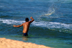 Man Throwing a fishing net in Hawaii. A man casting a fishing net near the shore in Hawaii. New fishing laws have been instituted in Hawaii limiting the amount stock photo