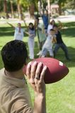 Man throwing football to group of people back view. Stock Photo