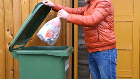 Man throwing garbage into litter-box in outside stock video footage