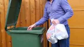 Man throwing garbage into litter-box in outside stock video