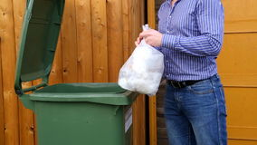 Man throwing garbage into litter-box in outside