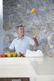 Man Throwing Orange Into Air At Kitchen Counter Royalty Free Stock Photos