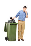 Man throwing out a stinky bag of trash. Full length portrait of a man throwing out a stinky bag of trash isolated on white background stock image