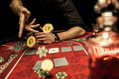 Man throwing poker chips on table while playing poker Stock Photo