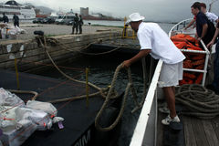 Man throwing rope. The sailor is throwing the rope to tie up the liberty boat in Brazil Stock Image