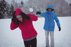 Man throwing snowball at woman Stock Photo