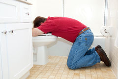 Man Throwing Up in Bathroom. Man on his knees in the bathroom, vomiting into the toilet Royalty Free Stock Images