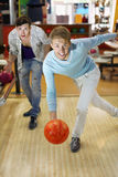 Man throws ball in bowling; friend supports his Royalty Free Stock Photo