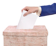 Man throws ballots into the ballot box. Man throws ballots into a ballot box against a white background Royalty Free Stock Photo