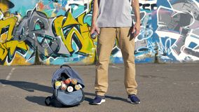 A graffiti artist throws and catches a paint can. A man throws and catches a spray paint can from one hand to another stock footage