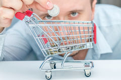 Man throws a coin into money box of the shape of trolley. Stock Photography