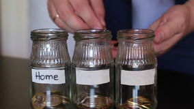 A man throws a coin in a piggy bank. On jars glued white stripes. stock footage