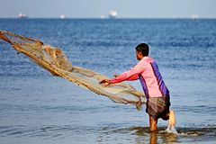 A man throws a fishing net. `Big fish, little fish, come on, come on!`. Morning fishing stock photo