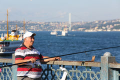 Man throws a fishing rod from the Galata Bridge Stock Photo