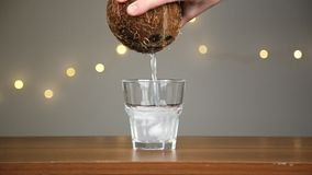 Man throws ice into a glass, then pours coconut water. Against the background of the lights stock video footage