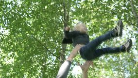 A man throws a little girl high up to the sky while walking in the forest stock video footage