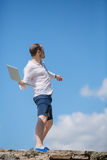 Man throws notebook against blue sky Royalty Free Stock Image