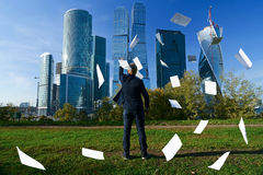 Man throws paper sheets. The person throws standard sheets in the afternoon against the business center Royalty Free Stock Photos