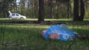 A man throws rubbish in the woods, close-up, trash. Forest stock video footage