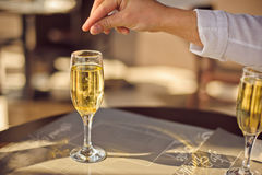 Man throws wedding ring in glass of champagne Stock Photography