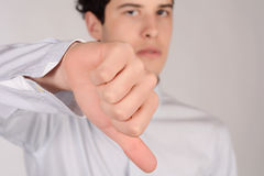 Man with thumb down. Portrait of young man with thumb down. Isolated white background Stock Images