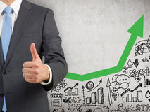 Man with thumb up and green graph. Close up of man's torso standing near concrete wall with startup icons and growing green graph. Concept of statistics. Toned Royalty Free Stock Image