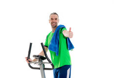 Man with thumb up train with fitness machine. Young man with thumb up train with fitness machine stock photo
